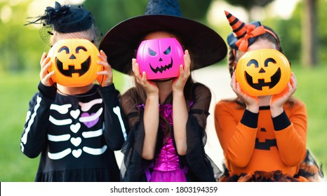 Happy Halloween! funny kids girls   in fancy dress hide their heads behind buckets pumpkins outdoors