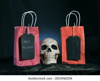 Happy Halloween gift bags on dark background with horror human skull medium shot