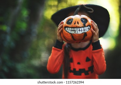 Happy Halloween! horrible creepy child girl in  pumpkin costume  in the forest
