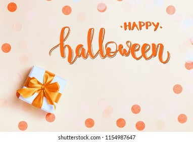 Happy Halloween lettering on orange holiday background with confetti and gift box. Top view, flat lay.