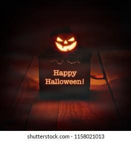 Happy Halloween lit candle on wooden floor