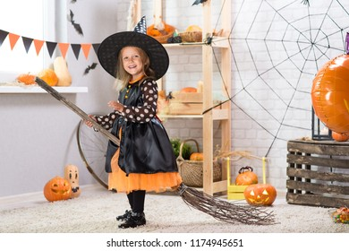 Happy Halloween. A little beautiful girl with broom in a witch costume celebrates a home in an interior with pumpkins