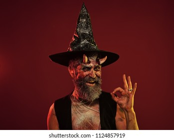 Happy Halloween man with devil horns in witch hat show ok. Satan hipster smile with beard, blood, wounds on red background. Hell, death, evil, horror concept. Might, magic, witchcraft