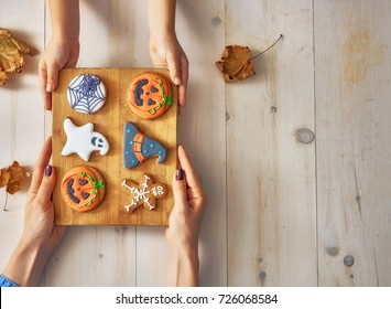 Happy halloween! A mother and daughter having festive sweets on the table in the home. Family preparing for holiday. Top view. Close up.