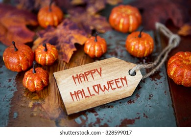 Happy Halloween on wooden tag with pumpkins and leaves