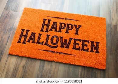 Happy Halloween Orange Welcome Mat On Wood Floor Background.
