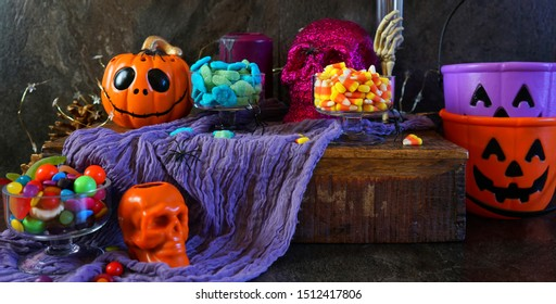 Happy Halloween party table with candy, pumpkins and skeleton candles, web banner.