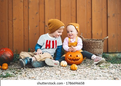 Happy Halloween! Photo of autumn mood with stylish girl and boy having fun in countryside. Kids party and celebration concept. Adorable little children with pumpkins on wooden barn background outside.