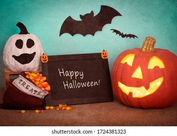 Happy Halloween Pumpkin Still Life Scene with sign board with text, ghost gourd, treats bag, against teal background with bats flying.  A horizontal photo with texture treatment.