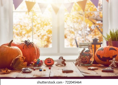 Happy Halloween! Pumpkin, sweets and cookies on the table in the home. Preparation for holiday.