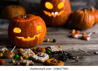 happy halloween pumpkins with glowing eyes, spiders, horror stories and more on a wooden background