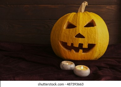 Happy Halloween .Scary pumpkin Jack-o-lantern and candles with candle holders on a dark background. Template. The place to advertise.