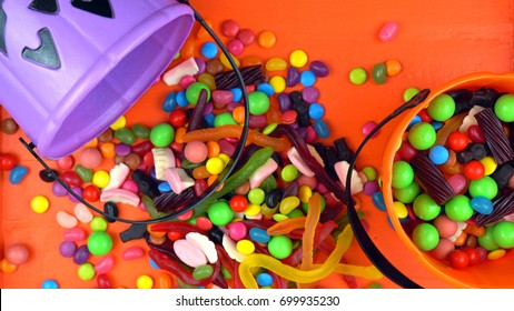 Happy Halloween Trick or Treat candy overhead jack-o-lantern buckets on bright orange wood table background.