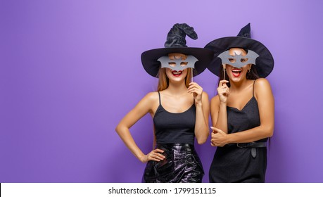 Happy Halloween! Two young women in black witch costumes on party on purple color background.