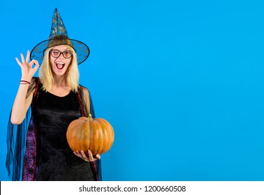 Happy halloween witch with pumpkin shows sign ok. Holiday halloween carnival costume. Witch magic. Jack-o-lantern. Sexy girl in halloween costume. Witch hat. Wizard. Secrets of magic. Halloween party.