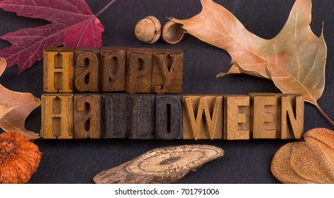 Happy Halloween wooden sign with a border of autumn decorations on a black background