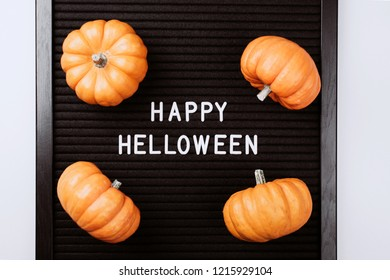 Happy Halloween words on black letter textured board. It is in frame with small yellow pumpkins. Flat lay style.