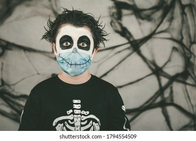 Happy Halloween.Close-up of kid wearing medical mask in a skeleton costume overgray background