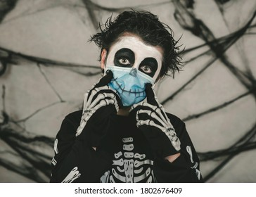 Happy Halloween,kid wearing medical mask in a skeleton costume making smile over gray background