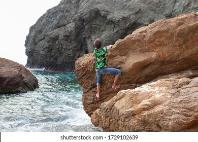 Happy hamdsome teen walks along the sea coast against the background of the sea, from behind a beautiful landscape