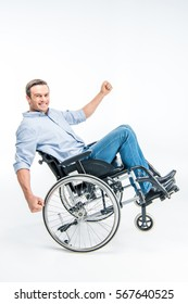 Happy handicapped man in wheelchair looking at camera isolated on white