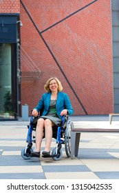 happy handicapped woman on wheelchair on square in the city