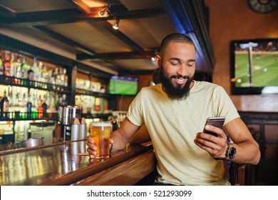 Happy handsome african american young man drinking beer in bar and using smartphone