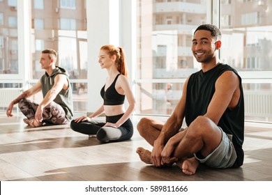 Happy handsome african american young man sitting and doing yoga in group in studio