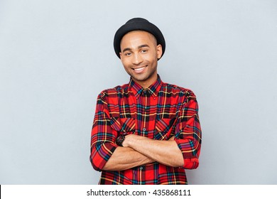 Happy handsome african man in hat standing with arms crossed