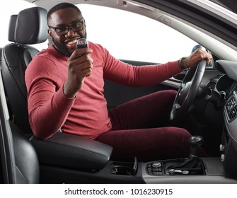 Happy handsome African man showing car keys in his newly bought auto smiling cheerfully sitting in the  luxury vehicle copy space owner ownership sales driving consumerism private taxi concept