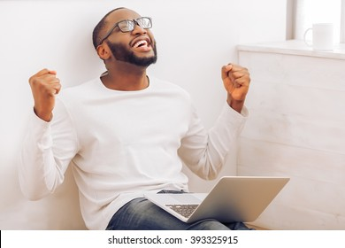 Happy handsome Afro American man in glasses is using a laptop, keeping hands in fists and smiling while sitting at home