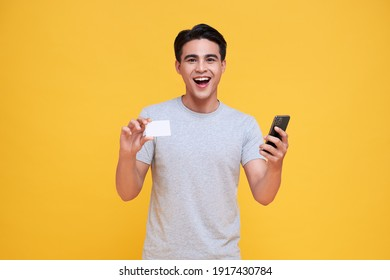 Happy handsome Asian man showing credit card and smartphone in hand isolated on yellow background.