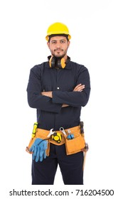Happy handsome beard worker smiling and standing confidently, guy wearing dark blue workwear and belt equipment with yellow helmet, isolated on white background