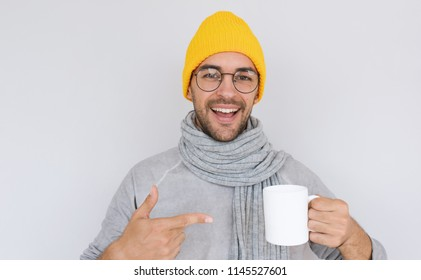 Happy handsome bearded male with white cup of tea wearing yellow hat and gray sweater with scarf in autumn or winter. Cheerful smiling man advertising something on white mug. Healthy, medicine, people