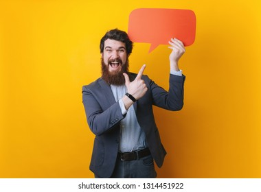 Happy handsome bearded man in casual  jacket pointing with finger on empty speech banner on yellow background