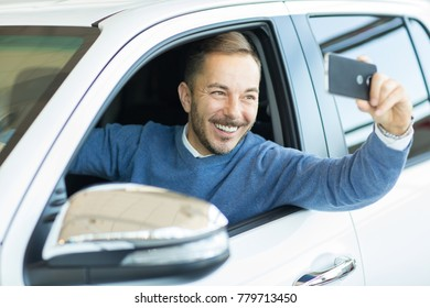 Happy handsome bearded mature man taking a selfie using his smart phone sitting in his new car people lifestyle device gadget social media technology positivity buyer client customer driver