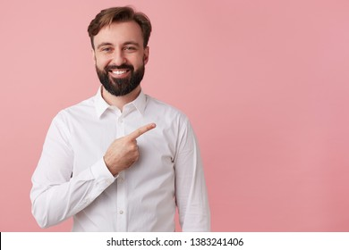 Happy handsome bearded young man, wearing a white shirt. Wants to tell cool news. Broadly smiling, draws your attention pointing to the copy space on the right; isolated over pink background.