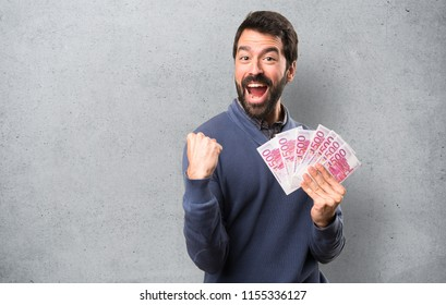 Happy Handsome brunette man with beard taking a lot of money on textured background