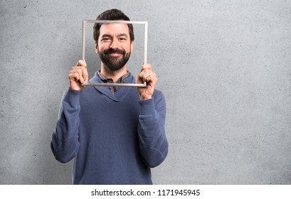 Happy Handsome brunette man with beard with framework on textured background