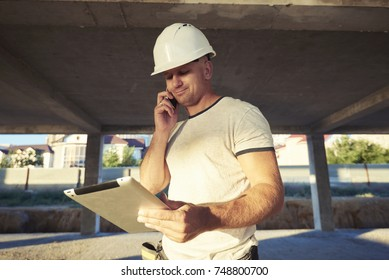 Happy handsome builder doing a call gesture with hand while holding touch pad. Business man or engineer conducts talks on the phone and holding a tablet with the plan or contract.