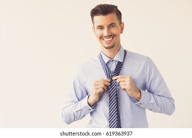 Happy Handsome Business Leader Knotting Tie