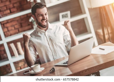 Happy handsome businessman is working with laptop in cafe. Good news. Feel of victory!