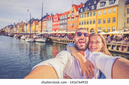 happy handsome couple in love taking a selfie photo in the typical famous area of Copenhagen with colourful houses called Nyhavn district. Traveling in Denmark concept