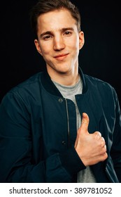 Happy handsome fashionable young man. Positive emotions. Thumb up. Black background
