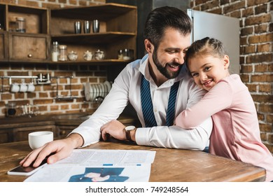 happy handsome father and little daughter embracing on kitchen
