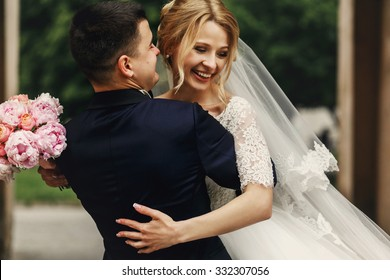 Happy handsome groom and blonde beautiful bride in white dress hugging under arc