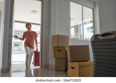 Happy handsome husband man open front door and carry luggage of new house with many moving boxes inside empty home. Family start new life. Real estate buy or purchase concept.