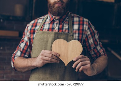 Happy handsome joiner in love holding and showing handmade wooden heart. He love his job.