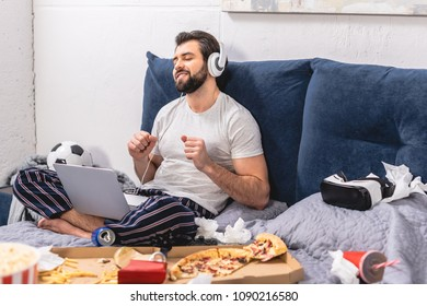 happy handsome loner listening music with laptop in bedroom