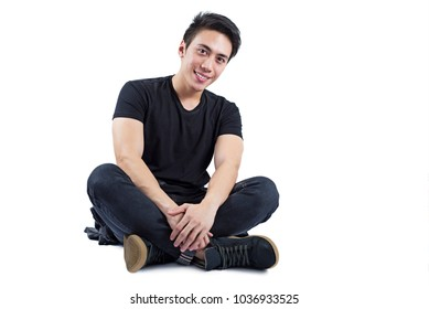 Happy handsome male model in sitting position over a white background.